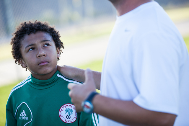Ten-year-old Lateef Omidiji Jr., left, listens as his coach, Esad Morina, speaks with the Review-Journal before Omidiji Jr.'s soccer practice at Russell Road Recreation Complex, 5901 E. Russell Rd ...