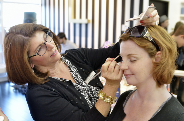 Anne Newman, U.S. sales manager for Kryolan Professional Make-up, left, applies eye shadow to Nichole Chandler during a grand opening at the L Makeup Institute at 5525 S. Decatur Blvd. in Las Vega ...
