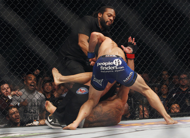 Referee Herb Dean jumps in to end the fight between Renan Barao and TJ Dillashaw during UFC 173 at the MGM Grand Garden Arena in Las Vegas on Saturday, May 24, 2014. (Jason Bean/Las Vegas Review-J ...