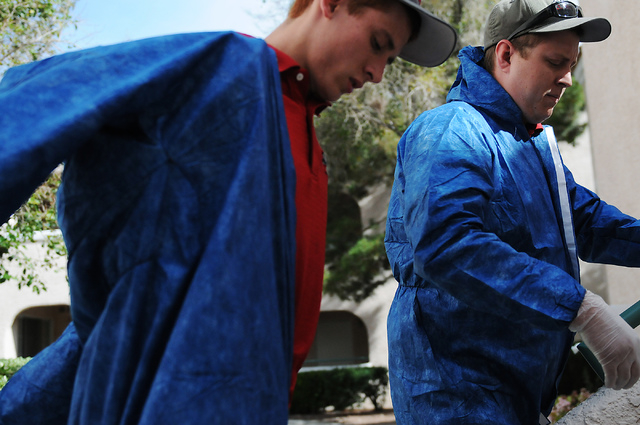 Jeremy Lines, left, and Travis Hoskins, technicians at Summit Restoration Inc., suit up before entering a job site for a mold remediation project inside a condominium at the Rain Tree West Complex ...