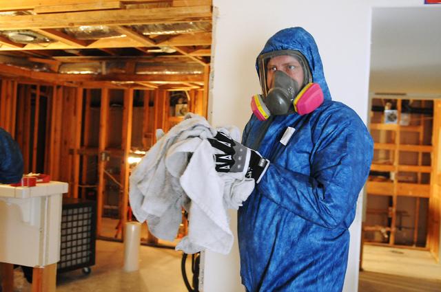 Travis Hoskins, technician at Summit Restoration Inc., removes dirty towels during a mold remediation project inside a condominium at the Rain Tree West Complex in Las Vegas Tuesday, April 15, 201 ...