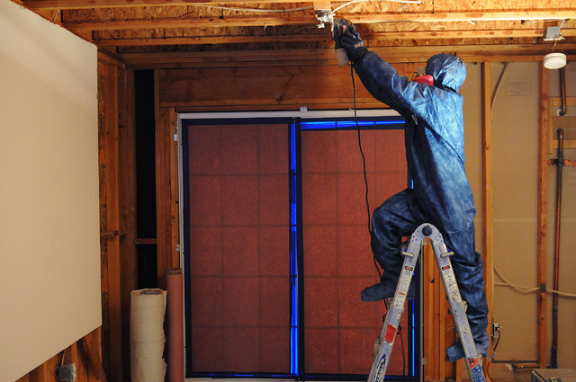 Jeff Dibble, technician at Summit Restoration Inc.,  resurfaces lumber during a mold remediation project inside a condominium at the Rain Tree West Complex in Las Vegas Tuesday, April 15, 2014. (E ...