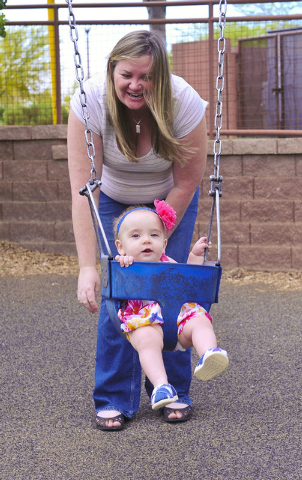 Kristina Moore plays with her daughter, Hailey, 9 months, at Butterfly Park in Las Vegas, Friday, April 25, 2014. Moore endured an emergency c-section and appendicitis on the same day.  (Jerry Hen ...