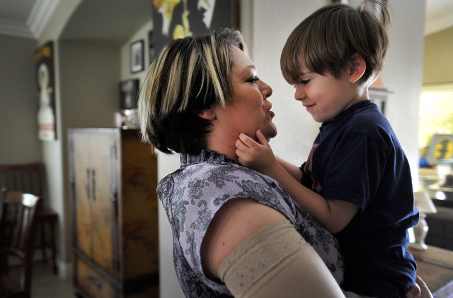 Jaylene Low, left, holds her son, Logan, 5, at their North Las Vegas home on Wednesday, April 23, 2014. Low has been cancer free for the last year since being diagnosed with breast cancer four yea ...
