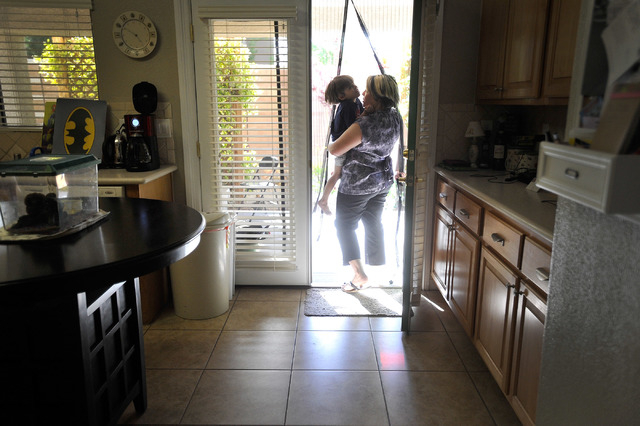 Jaylene Low holds her son, Logan, 5, as they go out the backdoor at their North Las Vegas home on Wednesday, April 23, 2014. Low has been cancer free for the last year since being diagnosed with b ...