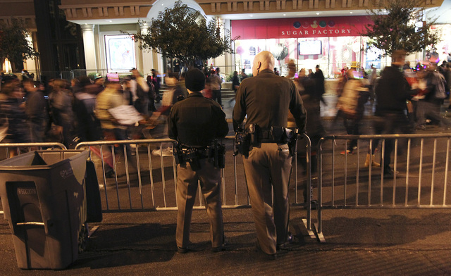 Metro Officers Nate Jones, left, and Paul Hunter watch as people go by on the Las Vegas Strip during the New Year's Eve celebration on the Las Vegas Strip on Dec. 31, 2012. (Jason Bean/Las Vegas R ...