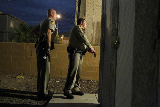 Las Vegas police officer Paul Hunter, left, and and unidentified officer check an apartment building, guns in hand, where shots were reported fired in Las Vegas Friday, Oct. 14, 2011. (John Locher ...