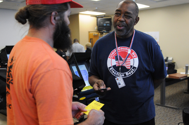 Program assistant instructor Matthew Goins, right, trains volunteer David Vargas on how to use a poll card activation machine during a poll worker training class at the Clark County Election Cente ...