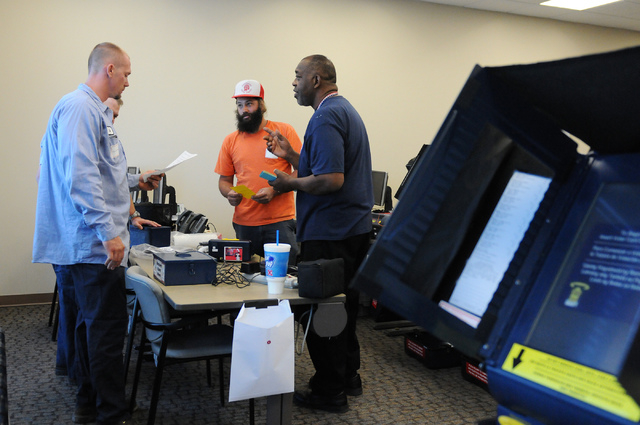Program assistant instructor Matthew Goins, from right, trains volunteers David Vargas and Cody Cunningham about how to assist voters during a poll worker training class at the Clark County Electi ...