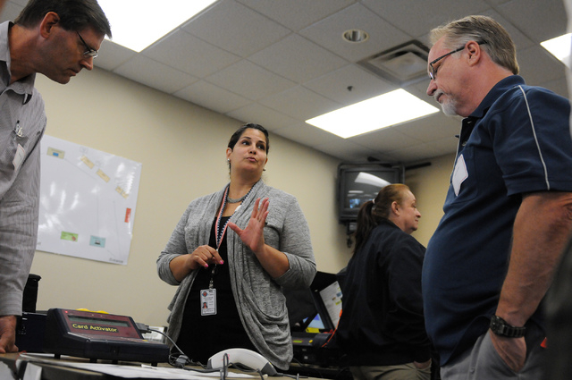 Program assistant instructor Yvette Dallas, center, trains volunteers Todd Myers, right, and Samuel Ingalls about handling poll card activation machines during a poll worker training class at the  ...
