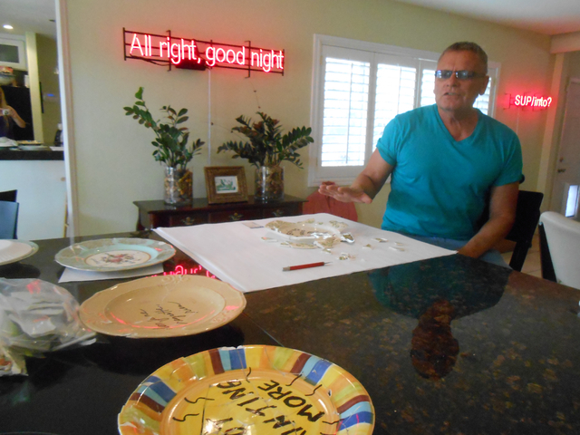 """Part of Richard Hooker's """"Pregnant Neon: A Tale of Conspicuous Devotion"""" exhibit at the Sahara West Library includes a section on regrets that includes shattered plates glued back together, se ..."""