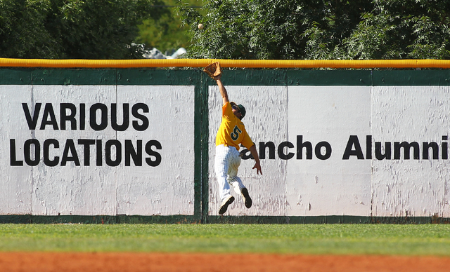 Rancho's David Modler makes a leaping catch before slamming into the left-field wall during the third inning Friday. The Rams beat Foothill, 13-3. (Chase Stevens/Las Vegas Review-Journal)