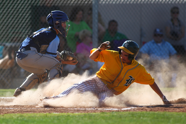 Rancho's Braulio Santiaguin slides safely into home during the third inning Friday as Foothill catcher Alex Elizondo fields the relay throw. Rancho won, 13-3. (Chase Stevens/Las Vegas Review-Journal)