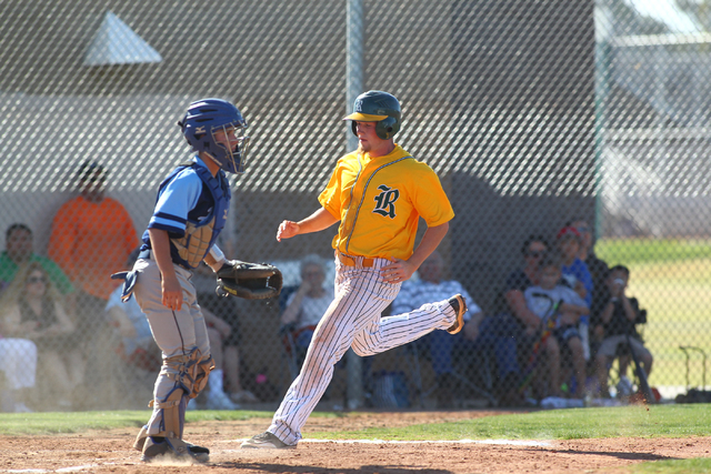 Rancho's Cody Suarez scores in the third inning of the Rams' 13-3 victory over Foothill on Friday as Falcons catcher Alex Elizondo looks on. (Chase Stevens/Las Vegas Review-Journal)