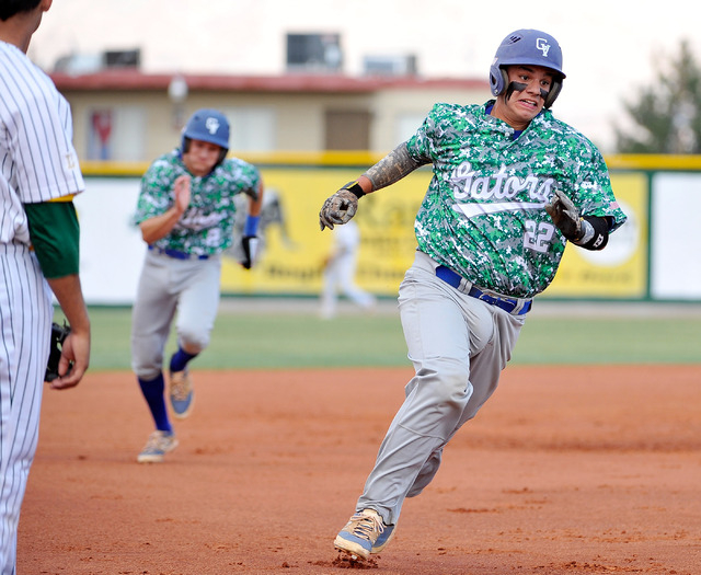 Green Valley's Ty Burger (22) and Jarod Penniman run home after a triple by teammate Cody Milner on Tuesday. The Gators won, 10-4. (David Becker/Las Vegas Review-Journal)