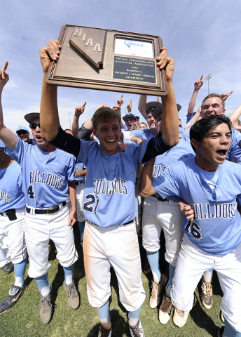 Centennial pitcher Cooper Powell holds up the Sunset Region championship trophy as the rest of the team celebrates its 3-1 win over Bishop Gorman on Saturday. (Josh Holmberg/Las Vegas Review Journal)