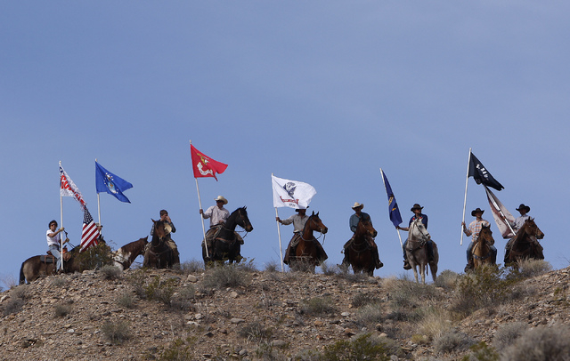 Supporters of rancher Cliven Bundy, fly flags on horseback  on a hill overlooking the protest site near Bunkerville on April 12, 2014. Moments before, the BLM agreed to cease the round up of the B ...