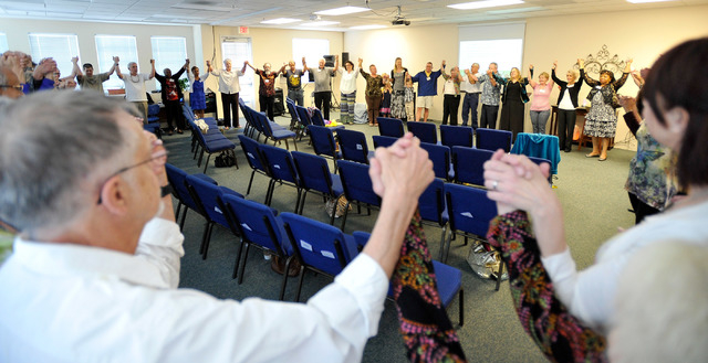 Congregants raise their hands as they join together to make a circle for a final prayer during the worship service at Unity Center in the Valley on Sunday, May 11, 2014. The weekly service feature ...