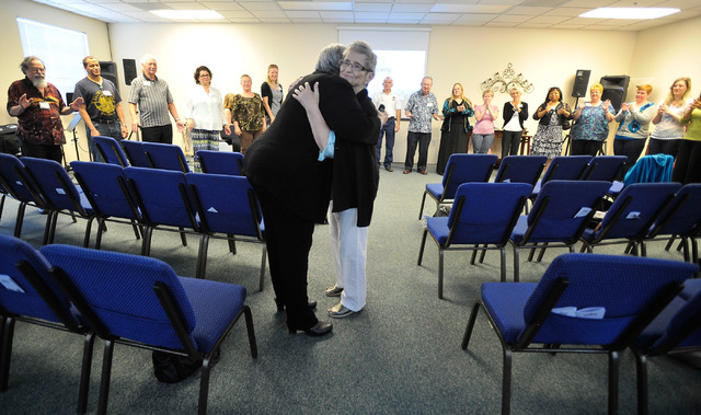 The Rev. Sophia Falke, left, embraces Joyce Feld one of the congregants during a circle for a final prayer at the worship service at Unity Center in the Valley on Sunday, May 11, 2014. The weekly  ...