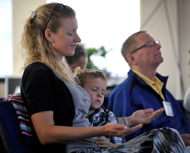 Laura Love, left,  meditates while holding her son, Cobalt, during the worship service at Unity Center in the Valley on Sunday, May 11, 2014. Ray Hanson is at right. The weekly service features mu ...