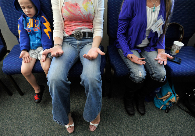 Congregants from left Max Botha, Holly Botha and Deidre Buss meditate during a worship service at Unity Center in the Valley on Sunday, May 11, 2014. The weekly service features music, a spiritual ...