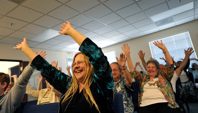 """Debra Hardy, left, does the """"happy dance"""" with other congregants during the worship service at Unity Center in the Valley on Sunday, May 11, 2014. The weekly service features music, a sp ..."""