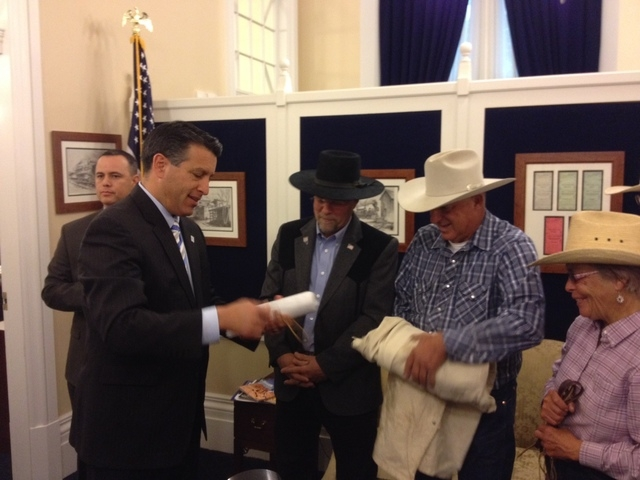 Gov. Brian Sandoval, left, accepts a petition on Friday, May 30, 2014, from Assemblyman Ira Hansen, R-Sparks, and ranchers Pete and Lynn Tomera. The three rode on horseback with 40 others to the C ...