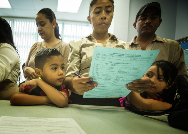 Fernando Alvarez, left, looks while his mother Lera registers for first grade at Cambeiro Elementary School. Cambeiro is one of 14 Clark County elementary schools that got a total of $19 million f ...