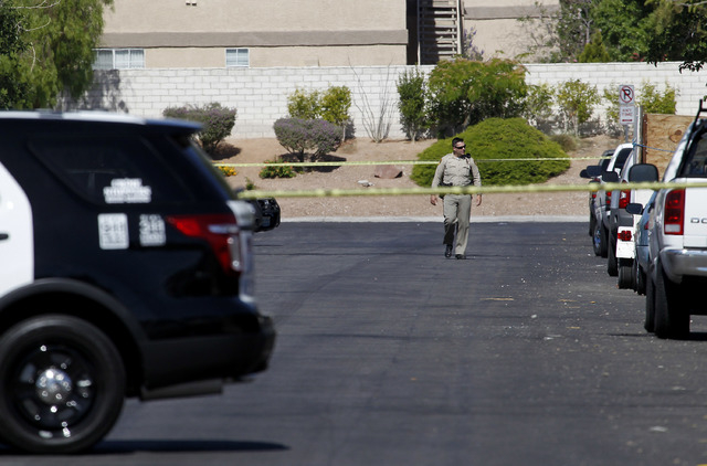 A Las Vegas Metropolitian police officer walks down Pebble Beach Boulevard near the scene of an apartment where an 11-year-old boy was shot in Las Vegas on Monday, May 26, 2014. (Justin Yurkanin/L ...