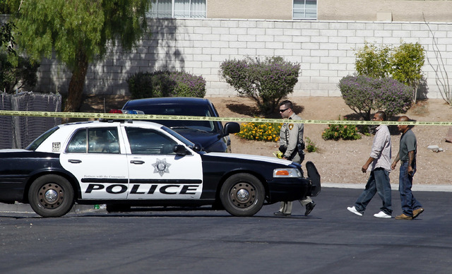 A Las Vegas Metropolitian police officer walks with some men down Pebble Beach Boulevard near the scene of an apartment where an 11-year-old boy was shot in Las Vegas on Monday, May 26, 2014. (Jus ...