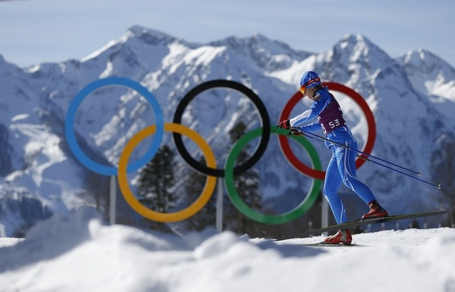 Greece's Panagiota Tsakiri passes by the Olympic rings in the cross country stadium before the start of the 2014 Winter Olympics in Krasnaya Polyana, Russia. (Felipe Dana/Associated Press)