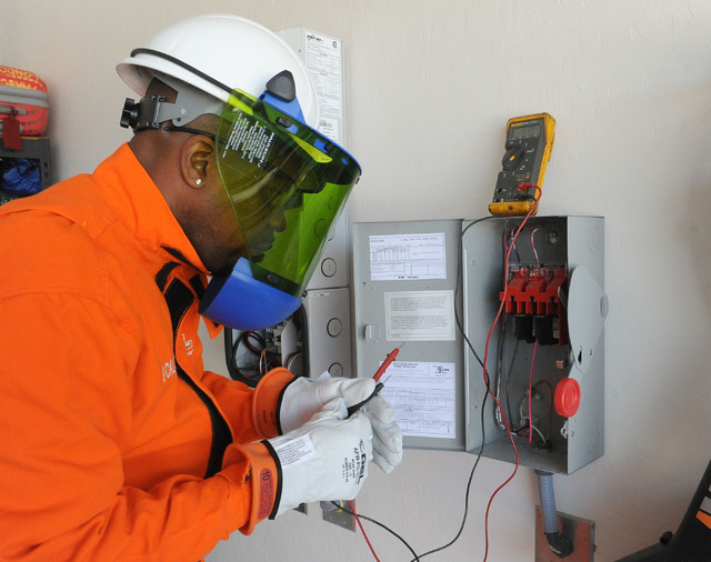 Marlon Burch, an employee of Solar City, checks out the electrical converter panel in the garage at the home of Ilene and Bill Graney in North Las Vegas, Wednesday, April 30, 2014.  The solar pane ...