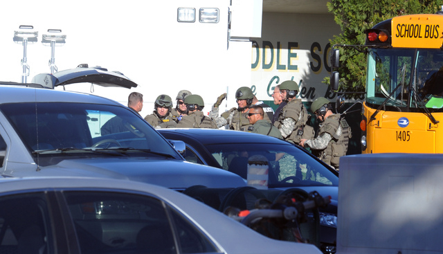 Law enforcement personnel gather at the scene of a shooting at Sparks Middle School in Sparks, Nev. on Monday, Oct. 21, 2013. A student at the school opened fire on campus just before the starting ...