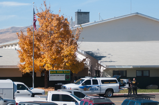 Police are staged in front of Sparks Middle School after a shooting in Sparks, Nev. on Monday, Oct. 21, 2013 in Sparks, Nev. A middle school student opened fire on campus just before the starting  ...