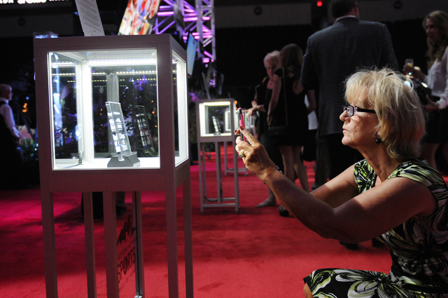 Kathy Lee takes a photo of the award presented to Tim Chambers as an inductee to the 2014 class of the Southern Nevada Sports Hall of Fame induction ceremony at the Orleans Arena in Las Vegas Frid ...