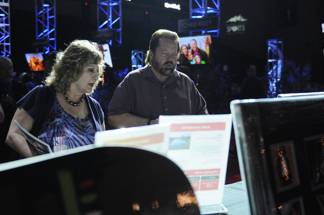 Linda Nordgren, left, and her husband Jim, browse silent auction items during the 2014 class of the Southern Nevada Sports Hall of Fame induction ceremony at the Orleans Arena in Las Vegas Friday, ...
