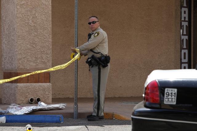 A Las Vegas police officer puts up crime scene tape in a parking lot on Sahara Avenue near Lamb Boulevard in Las Vegas Tuesday, May 6, 2014. (John Locher/Las Vegas Review-Journal)
