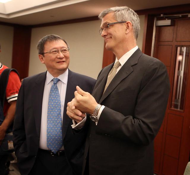 Hong Kong businessman Richard Suen,left, talks to Steve Jacobs, former Las Vegas Sands China CEO , before opening statements in Suen's lawsuit against Las Vegas Sands, Wednesday, April 3, 2013 in  ...