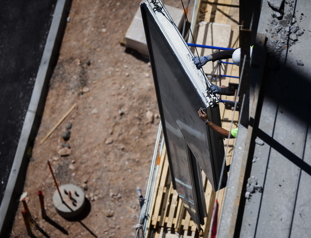 Construction workers grab a glass panel at One Summerlin  building at   Downtown Summerlin at Sahara Avenue and I-215 on Thursday, May 15, 2014. The first phase of the development will include 1.6 ...