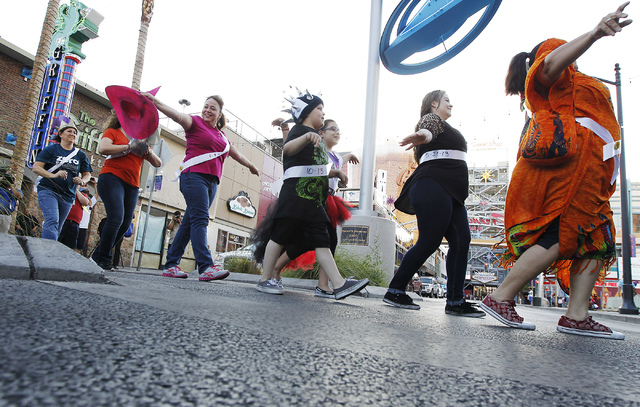 A flash mob is led across Fremont Street by the Crosswalk Crusader, not pictured, during an event aimed to increase driver awareness for pedestrians in Las Vegas on May 8, 2014. (Jason Bean/Las Ve ...