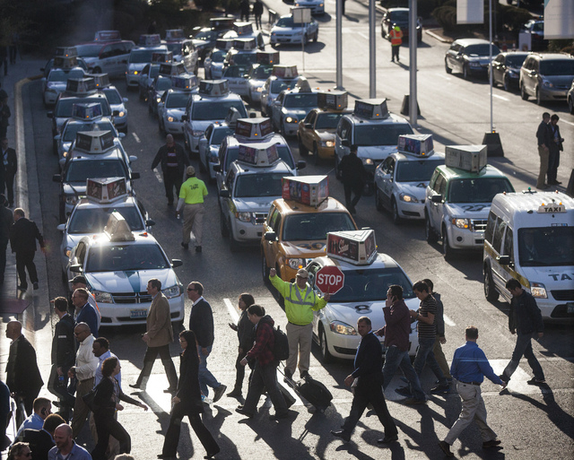 A man directs taxi traffic in front of Las Vegas Convention Center during CES on Wednesday, Jan. 8, 2014.  Uber, a rideshare and car-for-hire app that's popular in larger cities  isn't allowed ...