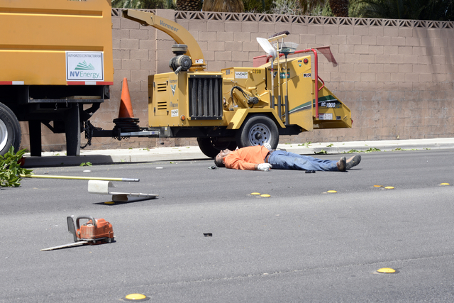 A man lies on the ground after falling from a tree-trimming basket near Sandhill and Russell Roads Friday, May 9, 2014. The man, an NV Energy subcontractor, was trimming trees around power lines a ...