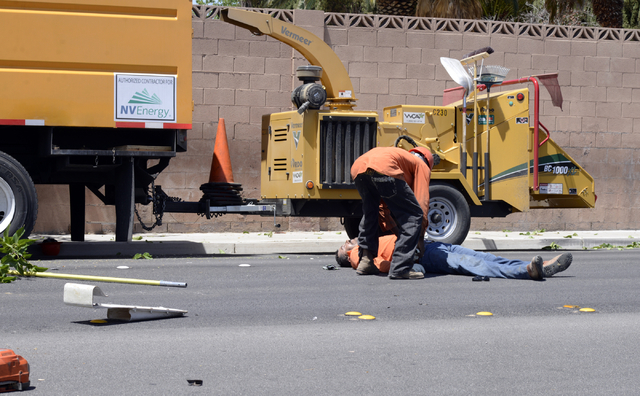A man is checked on by a co-worker after falling from a tree-trimming basket near Sandhill and Russell Roads Friday, May 9, 2014. The man, an NV Energy subcontractor, was trimming trees around pow ...