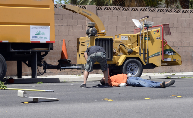 A man is checked on after falling from a tree-trimming basket near Sandhill and Russell Roads Friday, May 9, 2014. The man, an NV Energy subcontractor, was trimming trees around power lines along  ...