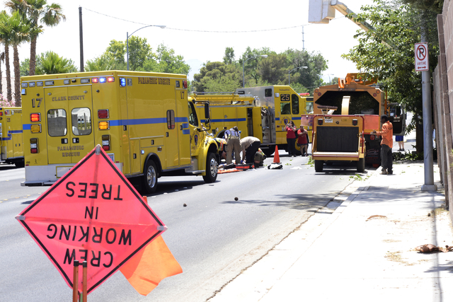 A man tended to by paramedics after falling from a tree-trimming basket near Sandhill and Russell Roads Friday, May 9, 2014. The man, an NV Energy subcontractor, was trimming trees around power li ...