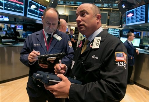 Trader Christopher Morie, right, works on the floor of the New York Stock Exchange, Tuesday, May 13, 2014. The Standard & Poor's 500 index crossed above 1,900 for the first time Tuesday as investo ...