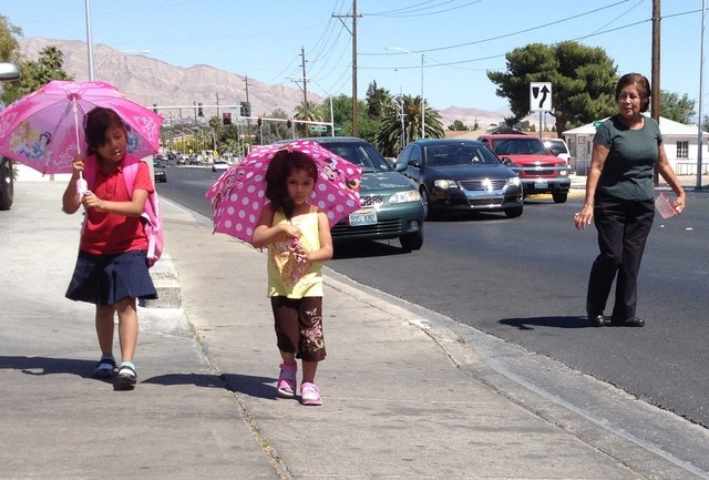 Ashley, left, and Kimberly Rivas walk along Bonanza Road near Bruce Street with their babysitter, Maria Ramirez, on Friday afternoon as temperatures climb in Las Vegas. Umbrellas may provide some  ...