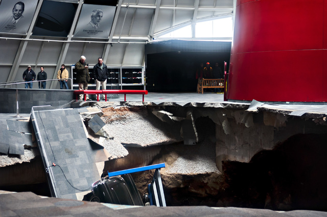 Officials view a sinkhole that opened up in the Skydome showroom, Wednesday, Feb. 12, 2014, at the National Corvette Museum in Bowling Green, Ky. Eight display cars were swallowed by the hole. (AP ...