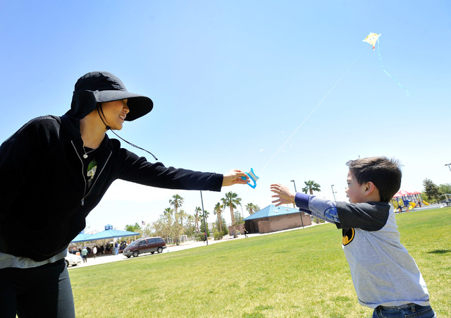 Sumi Esperanza, left, hands off a kite to her three-year-old son, Daniel while the two attended their church picnic at Lone Mountain Discovery Park on Sunday, May 11, 2014.  Gusty winds will conti ...