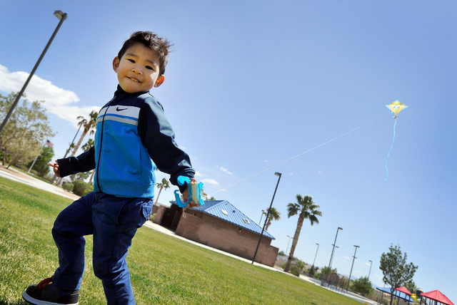 Jadon Esperanza, 2, flies a kite while he attended a church picnic with his family at Lone Mountain Discovery Park on Sunday, May 11, 2014.  Gusty winds will continue from the north on today and d ...